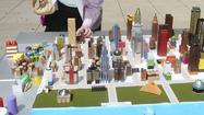 "At the Chicago Cultural Center, a young intern is stationed behind a tabletop model of downtown Chicago, miniature buildings made of painted wood blocks, old salt shakers and other odds and ends. There's even a tiny plastic cow. When people walk by, she invites them to play: ""You can redesign Chicago!"""