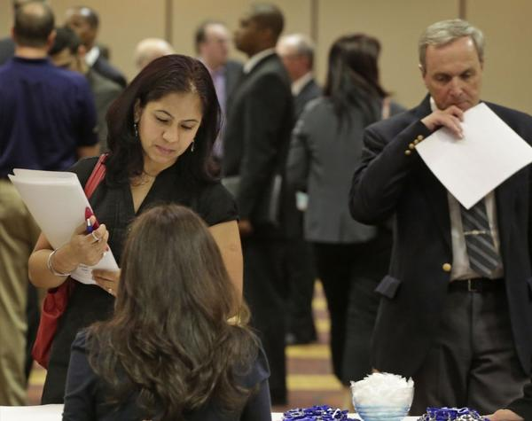 Job seeker Anu Vatal of Chicago speaks with a recruiter during a career fair in Rolling Meadows, Ill.