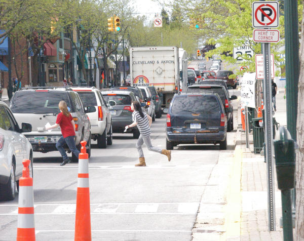 Two young women run through traffic stopped on Bridge Street in Charlevoix.