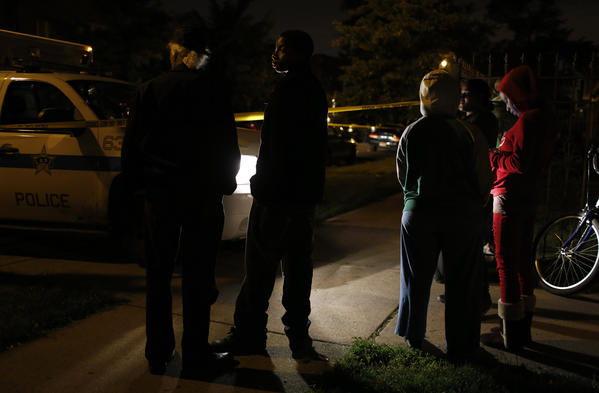 Residents stand and watch as Chicago police investigate a killing in the 6300 block of South Francisco Avenue in Chicago late Thursday.