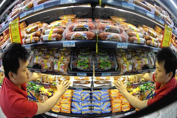 An employee is reflected in a mirror as he arranges a shelf displaying meat products of Shuanghui (Shineway) Group at a supermarket in Wuhan. Shuanghui International Holdings is buying Smithfield Foods Inc, the world's biggest hog producer, for $4.7 billion to feed a growing Chinese appetite for U.S. pork, in a deal that has stirred concern among U.S. politicians.