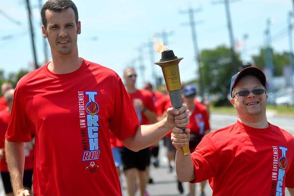 Laurel Police Officer Stephen Ivory, left, helps Special Olympian Ben Stevick, of Laurel, carry the torch through College Park as the Torch Run began its journey to Laurel June 5.