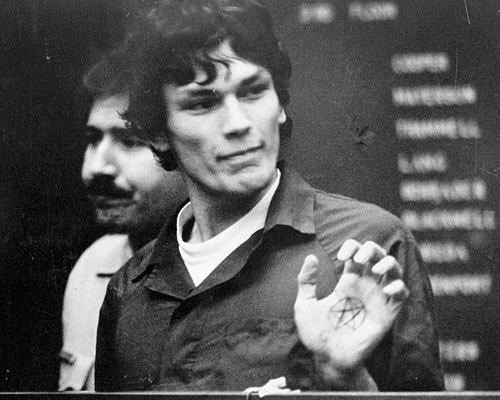 In court in 1985, Richard Ramirez flashes a pentagram drawn on the palm of his hand. Similar symbols were found in his car, his jail cell and at the Los Angeles area homes of some of his 13 torture-murder victims.