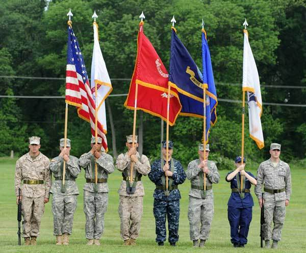 The color guard stands in a field waiting for the Armed Forces Day ceremony to begin.