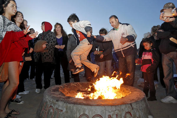 Kianoush Hamadani, center right, of Irvine, helps his son Cameron over a bonfire in celebration of the Persian New Year, known as Norooz, held at Corona del Mar State Beach.