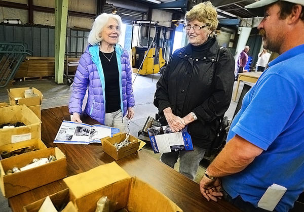 Nannette Guerin, left, of Chula Vista, Cal., and her sister-in-law, Florence Guerin, of Greencastle, shop for a spiral stair case with sales associate Paul Rhodes at the Duvinage Spiral and Circular Stairs company during a sale Friday in Hagerstown.