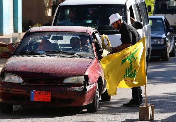 Hezbollah supporters in the Lebanese village of Bazzalieh distribute sweets to passersby to celebrate the fall of the Syrian town of Qusair to Hezbollah fighters and forces loyal to Syrian President Bashar Assad.