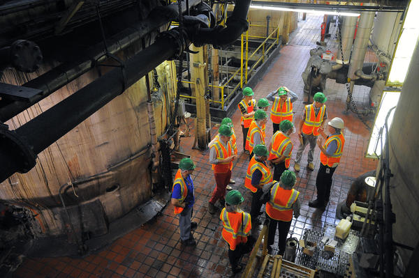 Baltimore, MD -- Visitors are dwarfed by among large machinery that churn product during a tour of Domino's Sugar refinery Tuesday, Jun. 4, 2013. (Karl Merton Ferron/Baltimore Sun Staff) [] (