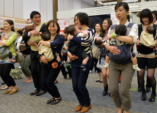 Parents samba dance with their babies at the Mama Fes event in Tokyo on May 17, 2013. Parents from other cultures may be more likely than Americans to develop a network to help with their children, one author says.