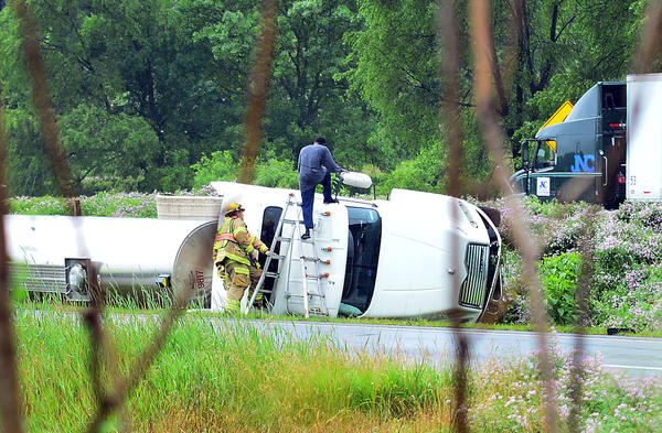 A man climbs up to enter the cab of an over-turned tank truck near the Route 40 exit on Interstate 70.