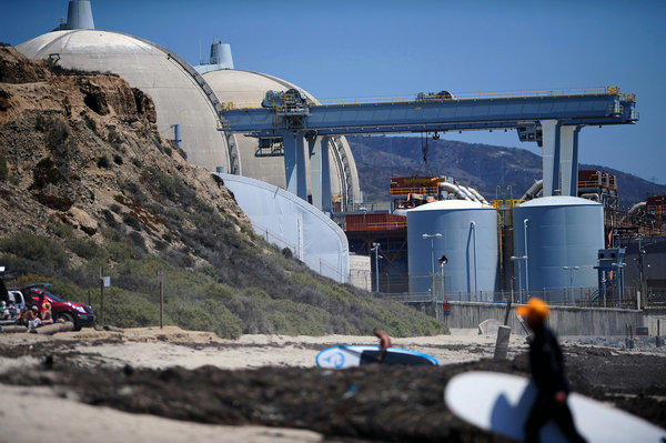 Surfers walk along a beach nearby the San Onofre nuclear power plant in 2012. Southern California Edison announced Friday that it would close the facility.