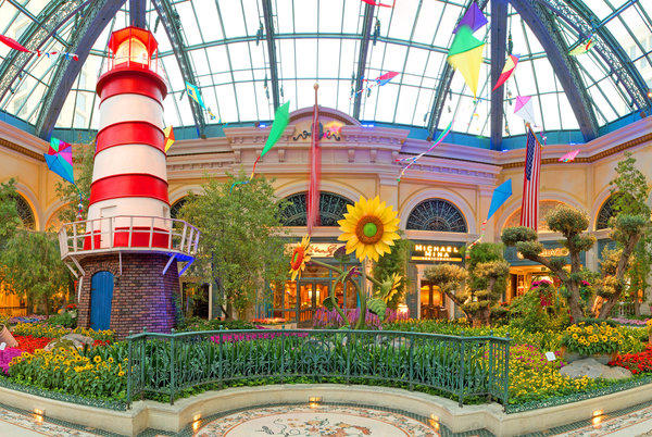 A red-and-white striped lighthouse beckons Vegas visitors to the colorful conservatory at Bellagio this summer.