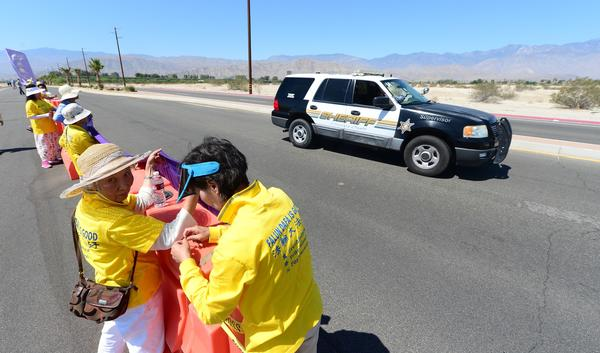 A police vehicle drives by as Falun Gong practitioners place banners on a barricade near where President Obama was meeting with Chinese President Xi Jinping in Rancho Mirage.