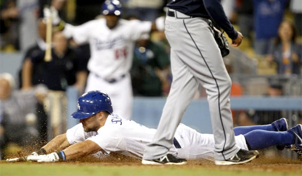 Skip Schumaker slides head-first into home plate on a wild pitch, giving the Dodgers a 2-1 victory in the 10th inning against the Atlanta Braves on Friday.