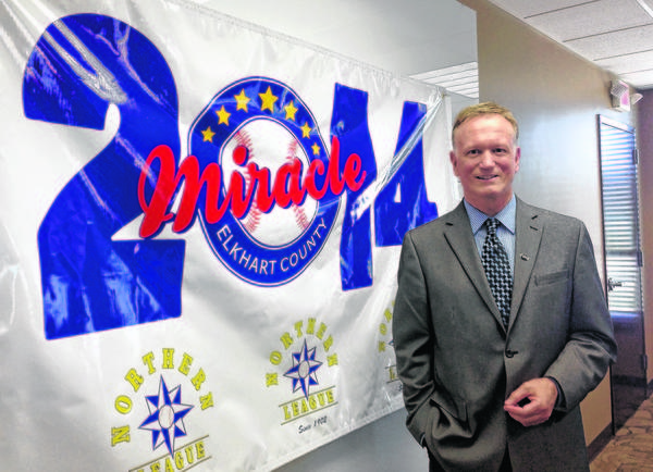 Craig Wallin, owner of the newly created Elkhart County Miracle, stands by the team's new banner, which was created by a Goshen College professor and art students.