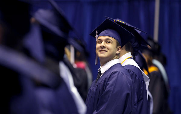 Denbigh High senior Ryan Thomas Cole Morris looks for family after filing in for graduation ceremonies Saturday at the Hampton University Convocation Center.