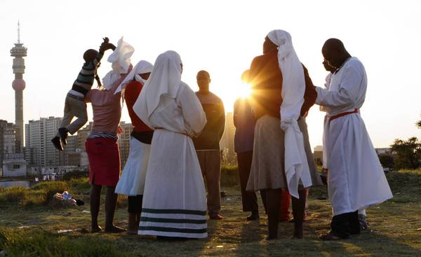 A church group prays Saturday for the health of former South African President Nelson Mandela on a hill in Johannesburg overlooking the city.