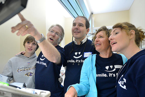 Dr. Bruce Burley, center, works with Dr. Richard Kramer, left, and his wife Dr, Lauren Kramer along with their two daughters Elizabeth, far left, and Gillian, far right, who are volunteering at the Dentistry From the Heart free dental care event at Hagerstown Smiles Saturday.