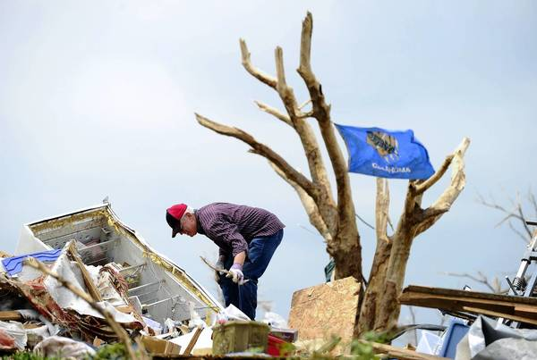 A tornado victim cleans debris from his home in Moore, Okla.
