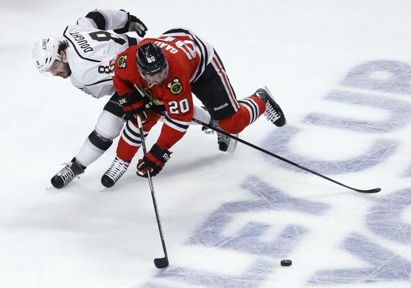 Kings defenseman Drew Doughty reaches around Blackhawks left wing Brandon Saad in an attempt to poke the puck away during the first period of Game 5 on Saturday evening at the United Center in Chicago.