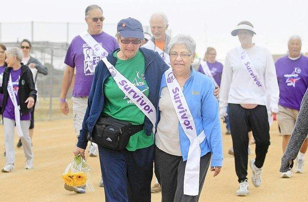 Cancer survivors Cheri Sheldon, center left, and Lena Enriguez, center right, walk around the track during Relay for Life, hosted by the American Cancer Society, at Costa Mesa High School on Saturday. Sheldon, a Costa Mesa High teacher, has been battling cancer since March 2012. Enriguez has been an ovarian cancer survivor for the last two years.