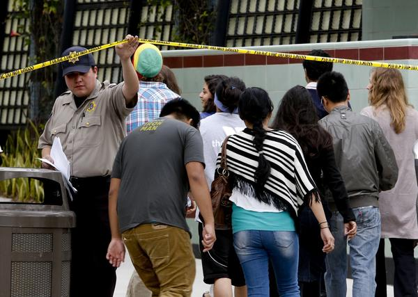 Students are escorted onto the campus of Santa Monica College on Saturday to get cars and belongings left behind when they evacuated during the shooting.
