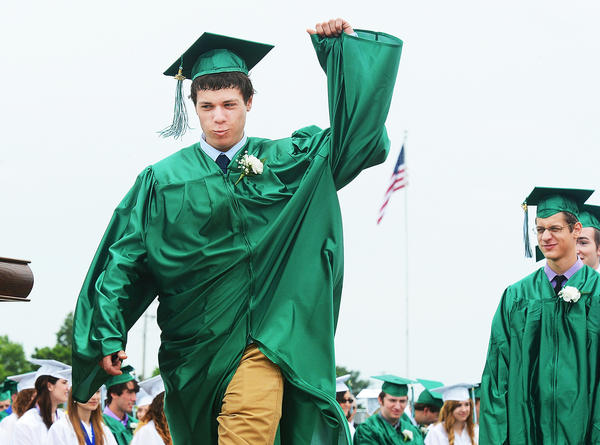Jonathan Glass raises his hand in acknowledgement of his name being called to receive his diploma during graduation excercises for the Class of 2013 at James Buchanan High School Saturday.