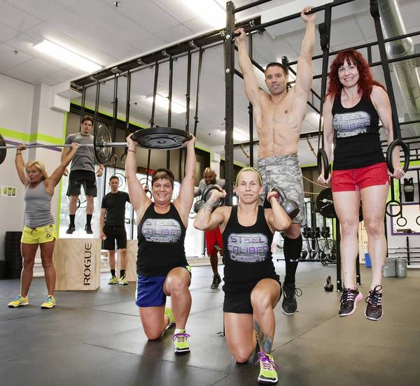 Steel Caliber CrossFit owners, foreground, from left to right, Francesca Ohl, Jennifer Washburn and Jesse Rehus, of Bethlehem along with Linda Paliaro, of Upper Nazareth Township, pose in the studio of their new location at 250 East Broad St., in Bethlehem on Thursday. They opened their fitness studio on May 1st and will be holding an open house on June 15th.