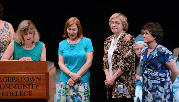Job Development Program teachers, right to left, Margie Wolverton, Betty Schriver and Nina Clopper hold back tears as Principal Amy Norris, left, announces their retirement at the graduation commencement Tuesday morning for Marshall Street School and Washington County Job Development Program.