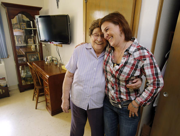 Jennifer Bohn, administrator of the Senior Citizens Home in Hosmer, right, shares a hug and a laugh with resident Emma Martel, left, in Martel's room at the facility. American News Photo by John Davis