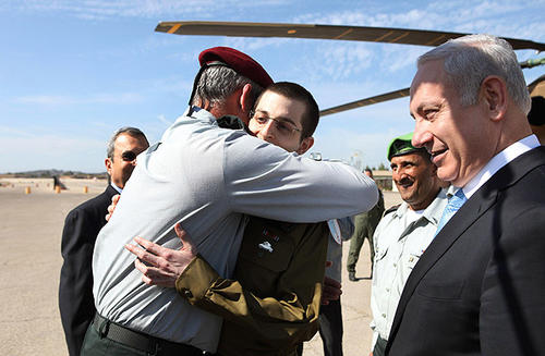 Israeli Chief of Staff Lt. Gen. Benny Gantz embraces released soldier Gilad Schalit upon his arrival at Tel Nof Airbase in southern Israel, where he was greeted by dignitaries including Prime Minister Benjamin Netanyahu, right, and Defense Minister Ehud Barak, partially obscured, left. Looking thin, weary and dazed, Schalit was released after more than five years in captivity in exchange for hundreds of Palestinian prisoners held by Israel.