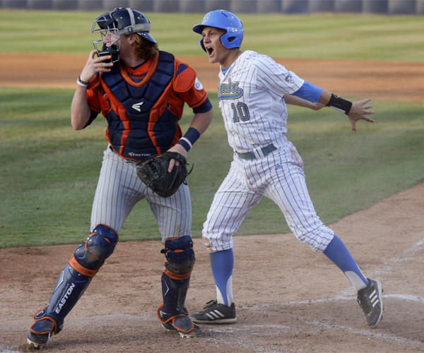 UCLA's Pat Valaika scores behind Cal State Fullerton catcher Chad Wallach during the first inning of the Bruins' 3-0 victory Saturday to earn a spot in the College World Series.