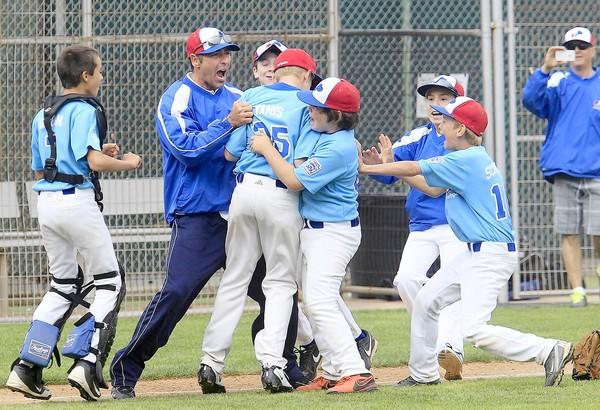 Earthpack head coach Jeff Fisher, second from left, celebrates with his players after they beat Dick's Sporting Goods in the Newport Beach Little League majors division championship game at Lincoln Elementary on Saturday.