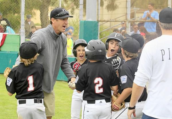 Pimco Manager Brady Butcher, top left, gathers his players after his team beat Murray Home Theater, 13-3, in the Newport Beach Little League Triple-A division championship game at Lincoln Elementary on Saturday.