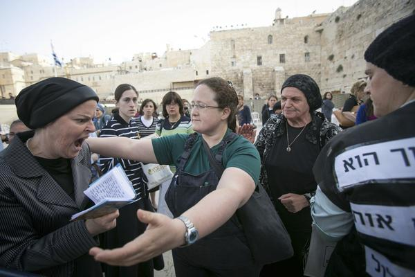 A member of the Women of the Wall organization attempts to hug an ultra-Orthodox protester Sunday at the Western Wall in Jerusalem.