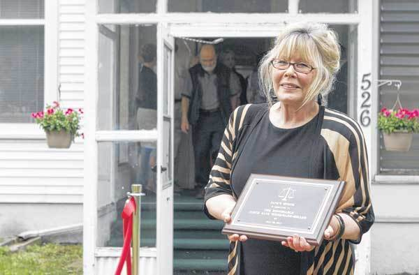 Judge Jane Woodward Miller holds the Jane's House dedication plaque in front of Jane's House in South Bend.