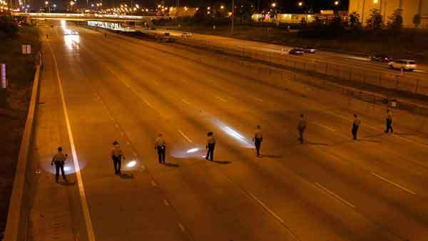 State police fan out across the southbound lanes of the Dan Ryan Expressway early Sunday morning looking for evidence from a shooting incident in which a man was killed and a woman wounded.