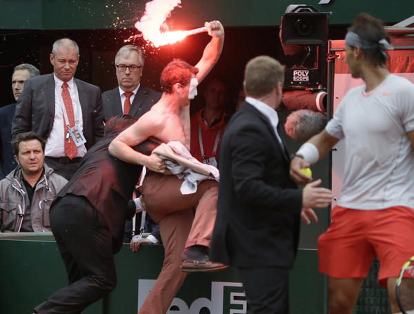 A protester is arrested after invading the court during the 2013 French tennis Open final.