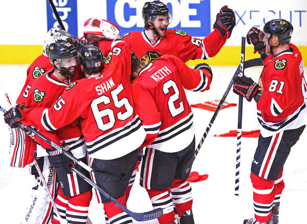 Blackhawks players gather around goalie Corey Crawford (50) to celebrate their 4-3 win against the Los Angeles Kings.