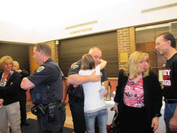 At the June 4 Tinley Park Villege Board meeting, Officer David Dorian embraces Carrie Iwasik, whose boyfriend, Thomas Mastro, 24, of Tinley Park, was allegedly shot and killed March 21 by Christopher Dyson, 18, during a fight over an online gaming system, according to prosecutors. Dorian was recognized with a commendation for his role in the arrest at the board meeting.