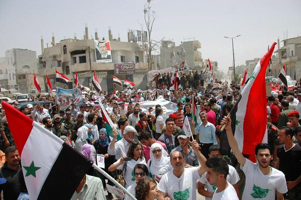 A celebration in the Syrian city of Qusair included bused-in government supporters, who waved flags to mark the town's retaking by forces loyal to President Bashar Assad.