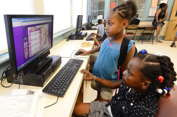 Nakiya Ford, standing at rear, 7, helps Honesty Mitchell, seated, 8, play the computer game Animal Shelter in the computer lab area of the Memorial Recreation Center in Hagerstown. The center's name will change to Robert W. Johnson Community Center this month.