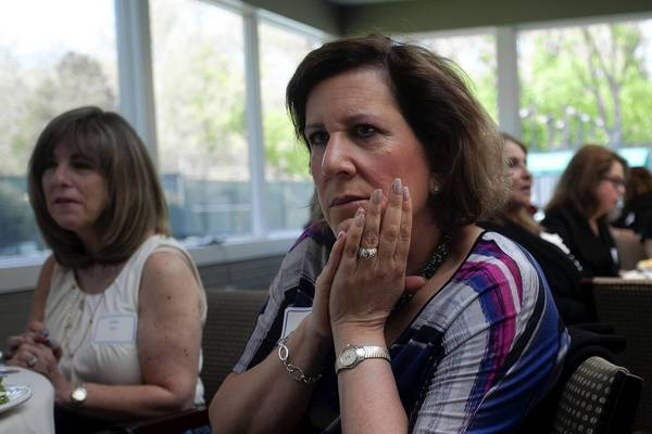 Sheila Domash listens to the Israeli national anthem May 14 during a meeting for daughters of Holocaust survivors at The Birchwood Club in Highland Park. Her parents, both Holocaust survivors, died in 2009.