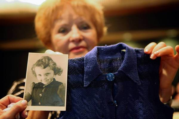 Holocaust survivor Barbara Cohen holds up a childhood photo and the vest she wore when she arrived in the U.S. during a Chicago ceremony to honor the 20th anniversary of the U.S. Holocaust Memorial Museum in Washington. She donated the items to the museum.