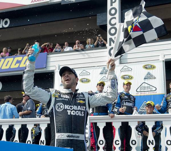 Jimmie Johnson holds the checkered flag in Victory Lane after winning the Party in the Poconos 500 NASCAR race at Pocono Raceway in Long Pond on Sunday.