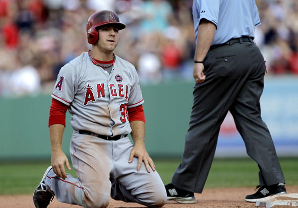 Angels outfielder J.B. Shuck kneels on the infield after being tagged out when he was caught in a rundown between second and third during the eighth inning against the Boston Red Sox.
