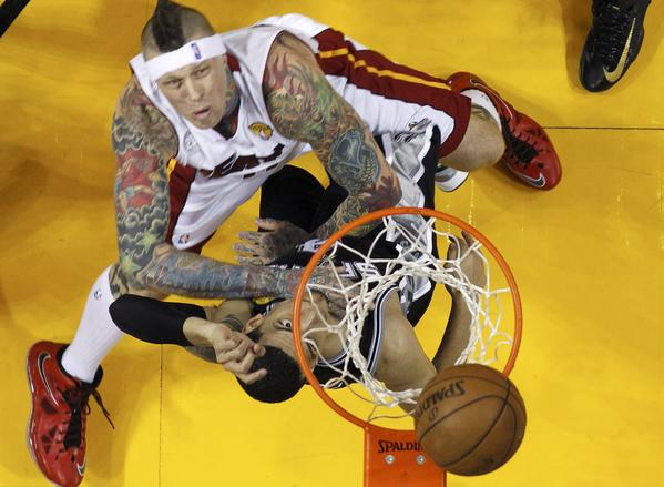 El delantero del Heat de Miami, Chris Andersen (con los tatuajes) y el francotirador de los Spurs de San Antonio, Danny Green pelean por un rebote durante la primera mitad del segundo partido de la final de la NBA, el domingo 9 de junio en Miami.