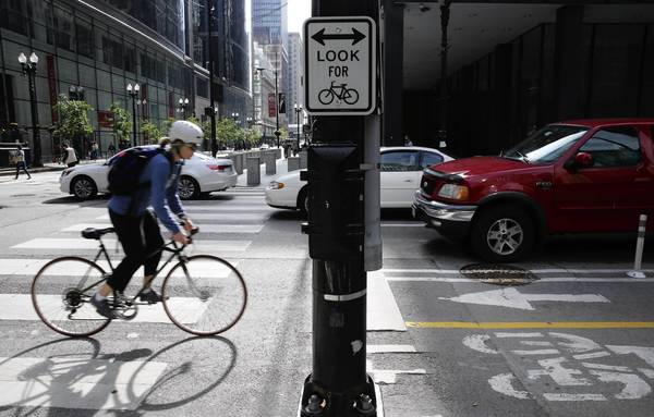 A sign warns pedestrians to look both ways for bicyclists when crossing the protected bike lanes at Dearborn and Washington streets in the Loop.