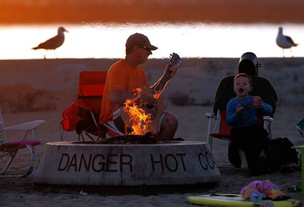 Newport Beach and the South Coast Air Quality Management District plan to test 10 fire rings that would run on an alternative fuel to wood at Corona de Mar State Beach and near the Balboa Pier. Above, a father and son sit by a fire at Corona del Mar State Beach.