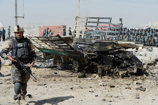 An member of the Afghan security forcse walks at the site of a suicide attack near the airport in Kabul.